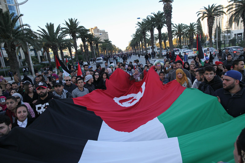 Marchers in the Tunisian capital Tunis carry a giant unified Palestinian and Tunisian flag during an 8 December 2017 protest of US President Donald Trump's recognition of Jerusalem as Israel's capital. Chedly Ben Ibrahim NurPhoto/Sipa USA